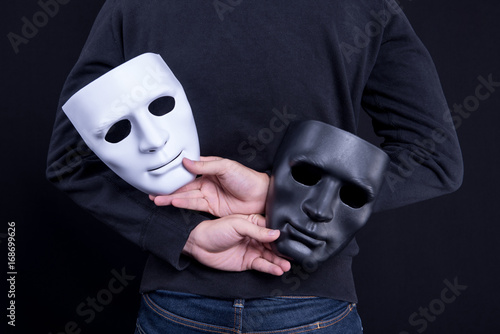 Fotografia Mystery man holding black and white mask