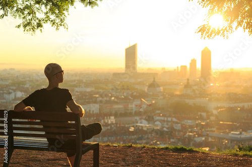 Stampa su Tela  A man on a bench in a park, relaxing and  enjoying the summer sunrise over a city