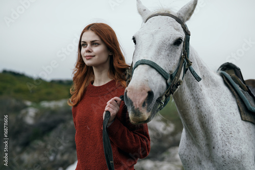 Beautiful young woman walking in the mountains with her horse