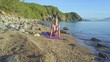 Blond Girl Planks in Yoga Pose on Pebble Beach by Wave
