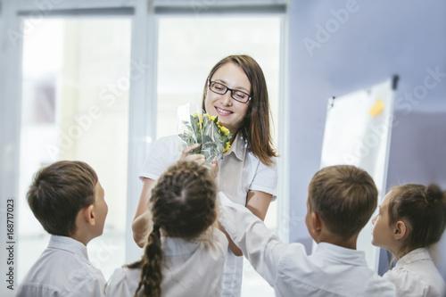 Zdjęcie XXL Piękne dzieci dzieci w wieku szkolnym z kwiatami dla nauczycieli w szkole