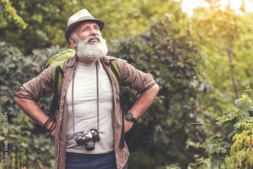 Exhausted senior male tourist resting after walking