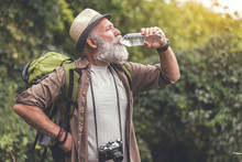 Tired Old Man Drinking Water From Bottle In Woodland