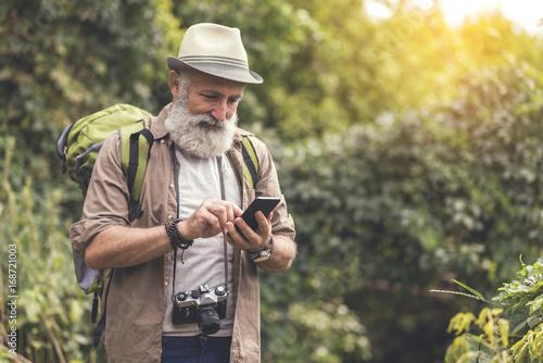 Fotografía  Glad mature male tourist using smartphone