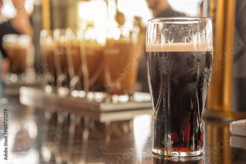 Fotografia Close up of a glass of stout beer in a bar