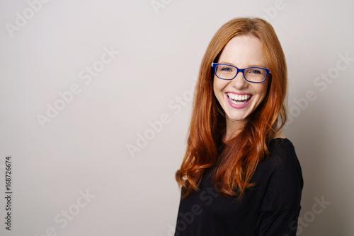 Fotografie, Obraz  lachende frau mit blauer brille vor grauer wand