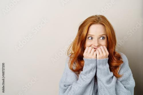 Leinwand Poster Frau blickt angespannt zur seite und hält die hände vor den mund