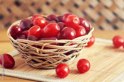 Fényképezés Fresh cornel berries (Cornus mas or Cornelian cherry) in woven basket