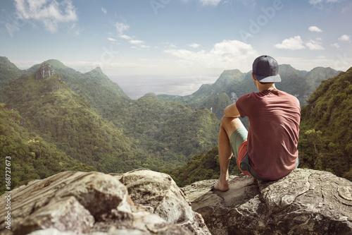 Fotografija  Junger Mann hat weiten Blick auf tropische Landschaft