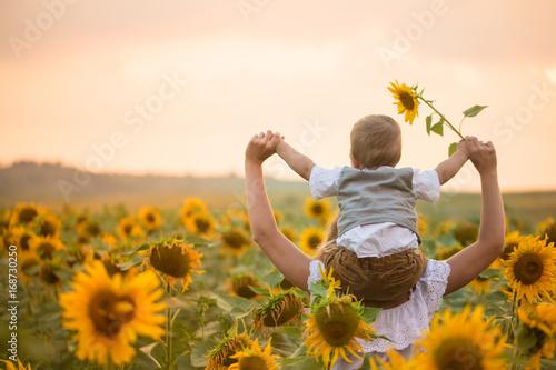 In de dag Zonnebloem Mother with baby son in sunflower field