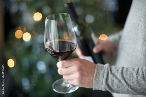 human hand holding wine glass. red wine, alcohol, celebration, temptation.