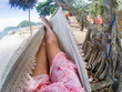 legs of woman relaxing in hammock on a tropical beach