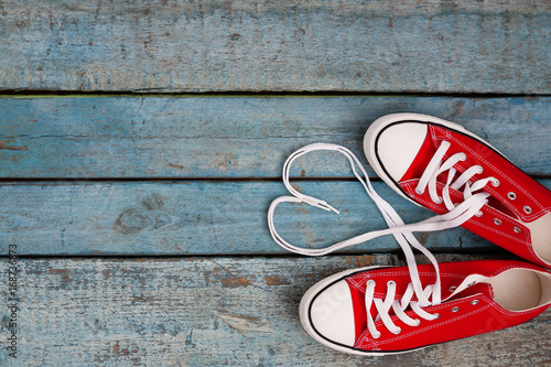Photographie A pair of red retro sneakers on a blue wooden background, laces lined in a heart shape