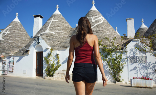 Back view of young woman choosing a trullo Wallpaper Mural
