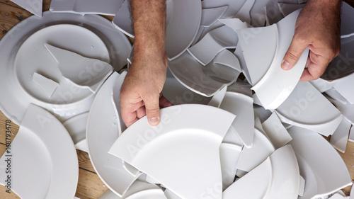 hands picking up broken white plates of floor