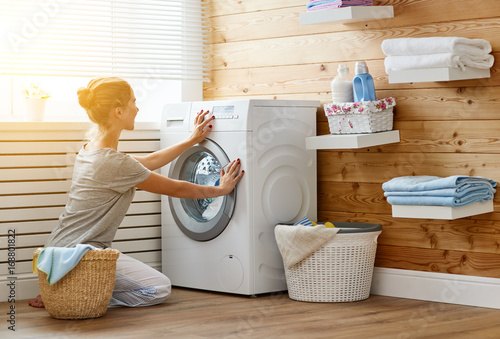 Photo  Happy housewife woman in laundry room with washing machine
