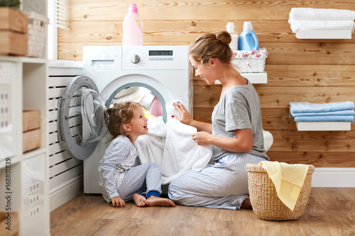 Photo  Happy family mother housewife and child   in laundry with washing machine
