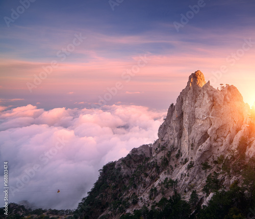 Poster Lichtroze Mountain landscape at sunset. Amazing view from mountain peak on the high rocks, blue sky, pink clouds and in the evening. Low clouds. Colorful nature background. Adventure. Travel in Crimea. Cliffs