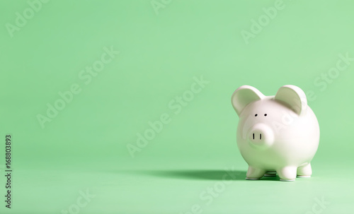 White piggy bank with glasses on a muted green background Canvas Print