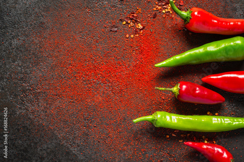 Red and green hot pepper and dry ground pepper on a dark background
