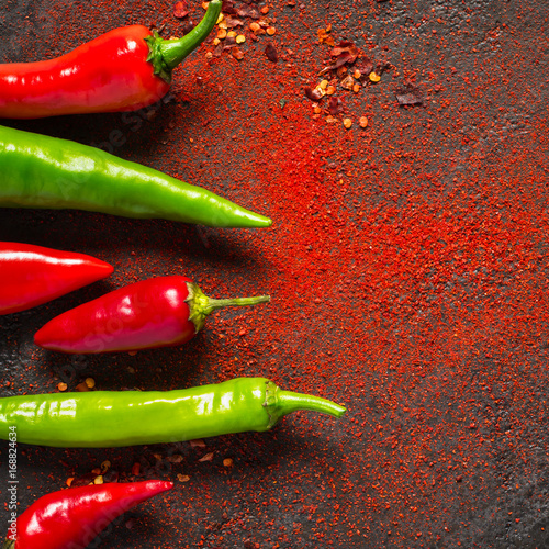 Staande foto Hot chili peppers Red and green hot pepper and dry ground pepper on a dark background