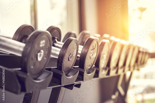 Photo Stands Fitness Rows of dumbbells in the gym with sunlight in morning.