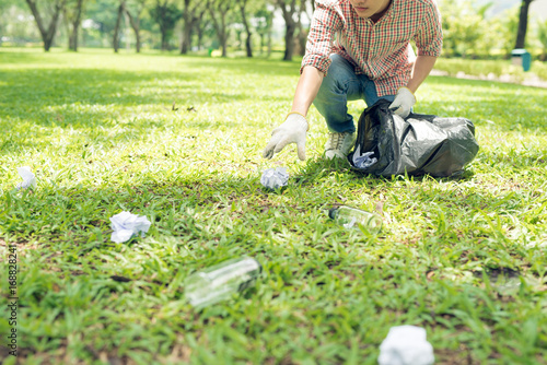 Fotografía  Young man crouching to waste and picking it up in bin bag