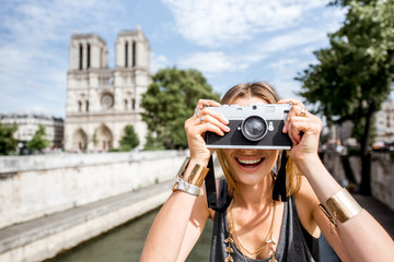 Young woman tourist photographing with camera standing in front of the famous Notre Dame cathedral in Paris