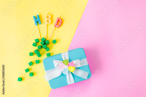 The Gift Box With Ribbon And Birthday Candles On Pastel Pink Yellow Colors Table Mix