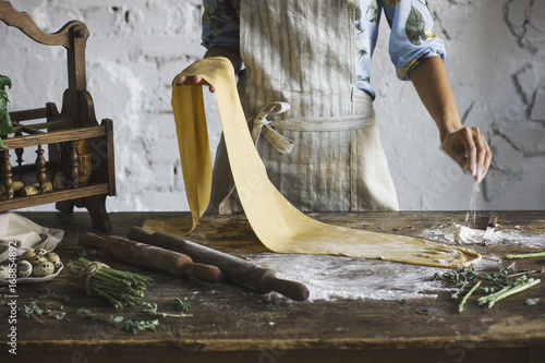 Fotografie, Obraz  Young woman in the apron preparing the dough for homemade pasta at rustic kitche