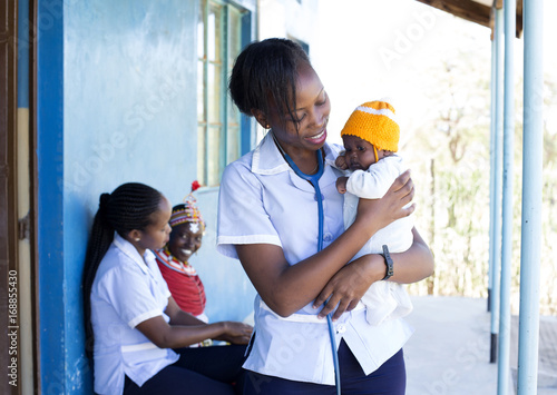 Nurses examining Mother and Baby in clinic. Kenya, Africa.