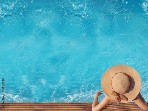 Top view of woman in straw hat relaxing in swimming pool at luxury villa resort. Summer holiday idyllic background. Vacations Concept. Exotic Paradise.