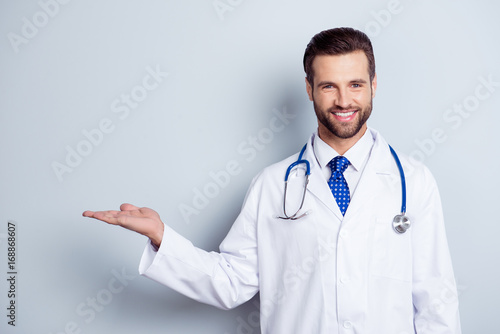Cheerful handsome bearded smiling guy is holding the copy space Fototapet