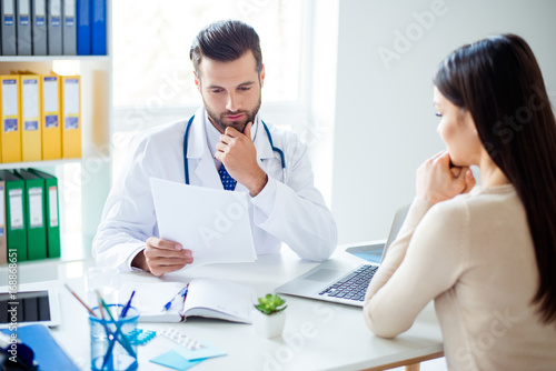 Young pensive doctor is consulting brunette female patient at his work station in clinic. He is in a white coat, reads the details of disease