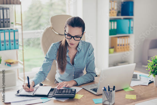 Portrait of serious young businesswoman accountant in formal wear and with pony Wallpaper Mural