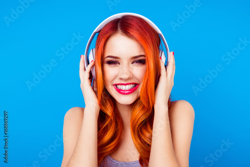 Fotografía  Dj turn on the music! Red head ginger young and very pretty girl is listening to music in big white earphones