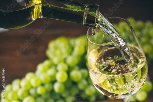 Fotografía  Pouring white wine into a glass with a bunch of green grapes against wooden back