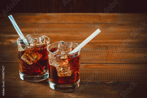 Fotografia  Beautiful cold drink of Cola with ice cubes with a boiler straws in glasses on wooden background with free space