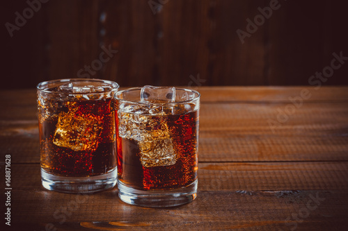 Fotografie, Obraz  Beautiful cold fizzy cola soda with cubes ice in glasses goblet on old wooden background with free space