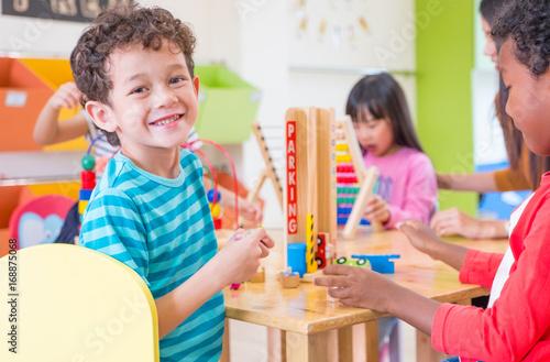 Fotografia, Obraz Kindergarten students smile when playing toy in playroom at preschool internatio