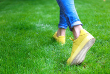Female Legs In Jeans And Yellow Sneakers On Green Grass