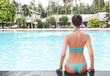 Beautiful young woman sitting on the edge of swimming pool at tropical resort