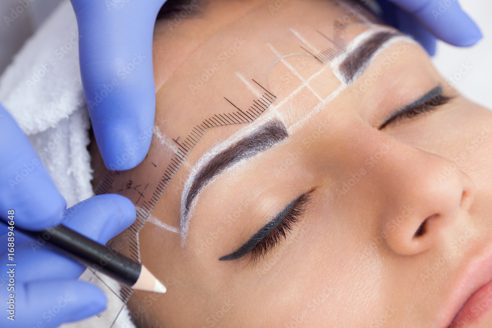Fototapety, obrazy: Permanent make-up for eyebrows of beautiful woman with thick brows in beauty salon. Closeup beautician doing  tattooing eyebrow.