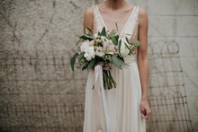 Bohemian Indie Bride In Simple Sparkle Top Wedding Dress And Feminine Pastel Bouquet With Ribbon