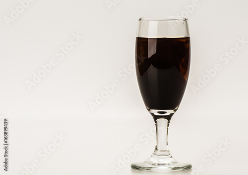Dark brown food coloring diffuse in water inside wine glass ...