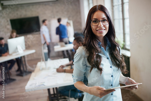 Portrait of young beautiful female designer holding tablet