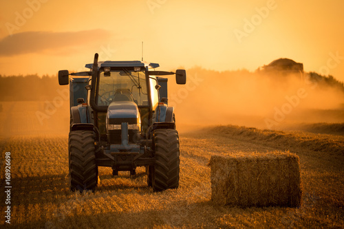 Fotografering  tractor sunset harvest