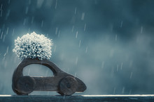 Car With A Bouquet Of Flowers On The Top. Wooden Toy Car With Flowers Rides In Rainy Weather. The Concept Of Flower Delivery. Copy Space For Your Text