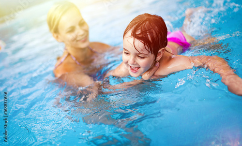 Valokuva  Beautiful woman with her daughter in swimming pool