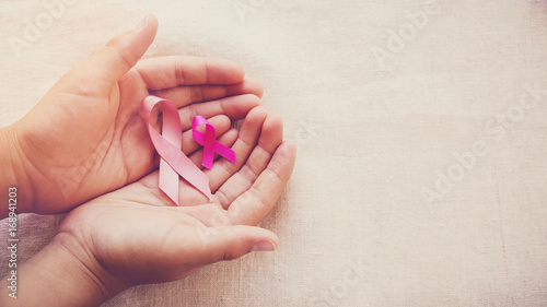 Hands holding Pink Ribbons toning background, Breast cancer